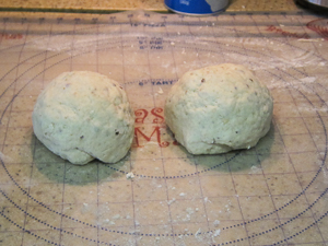 Cut dough in half forming two equal ball shapes.